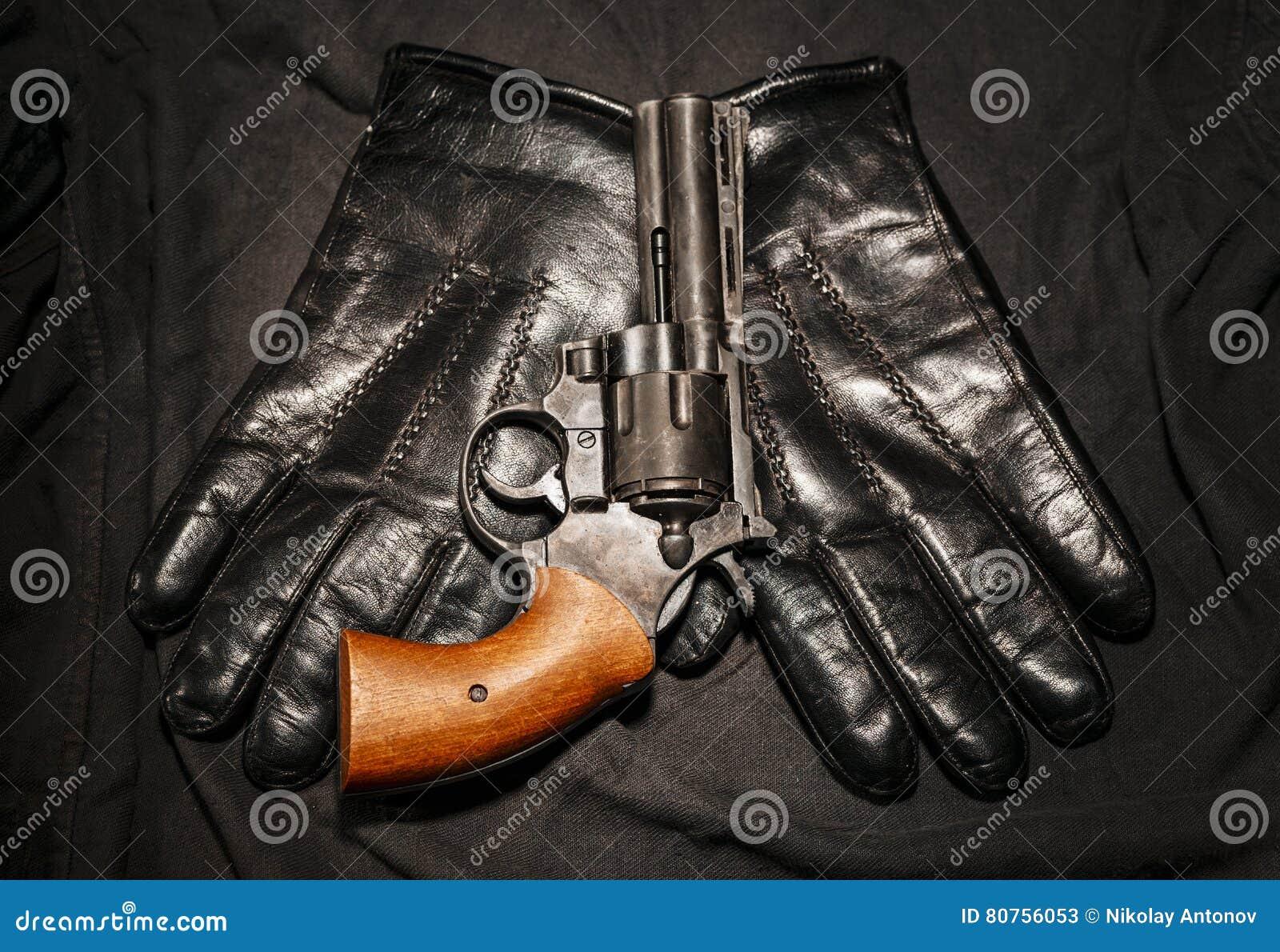 Het concept van de misdaad Zwart kanon met leerhandschoenen op donkere doek
