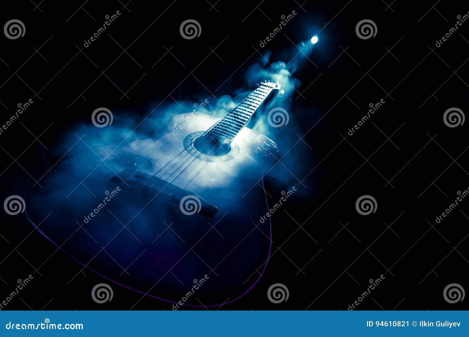 Het concept van de muziek Akoestische die gitaar op een donkere achtergrond onder lichtstraal met rook met exemplaarruimte wordt