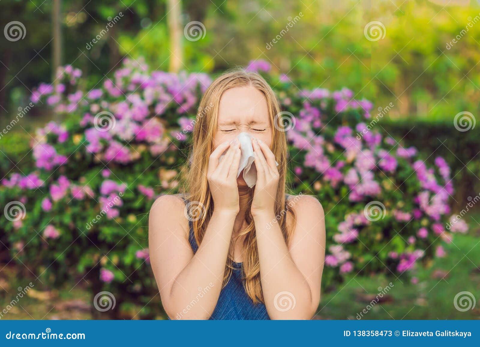 Het concept van de stuifmeelallergie De jonge vrouw gaat niezen Bloeiende bomen op achtergrond