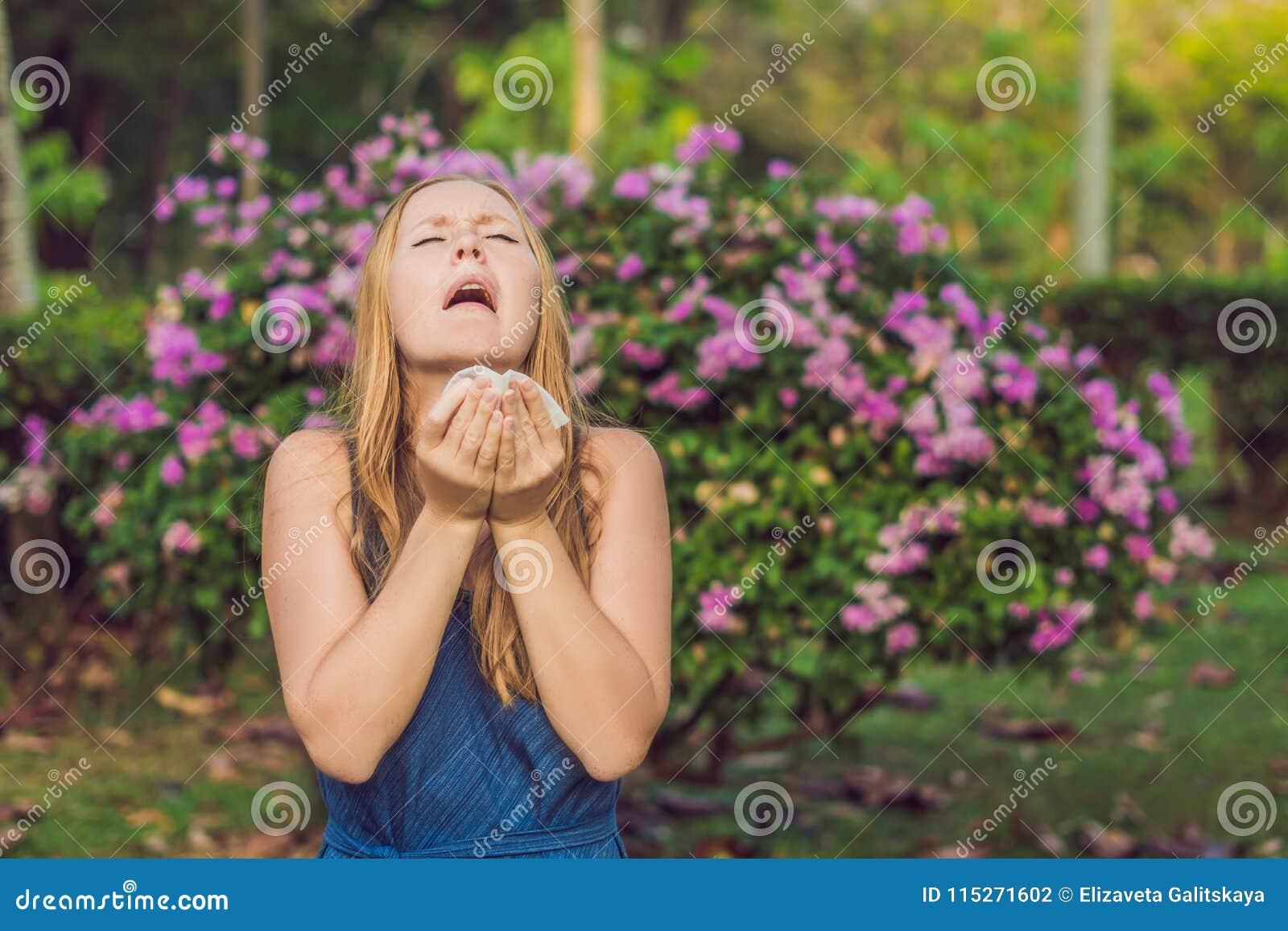 Het concept van de stuifmeelallergie De jonge vrouw gaat niezen Flowerin