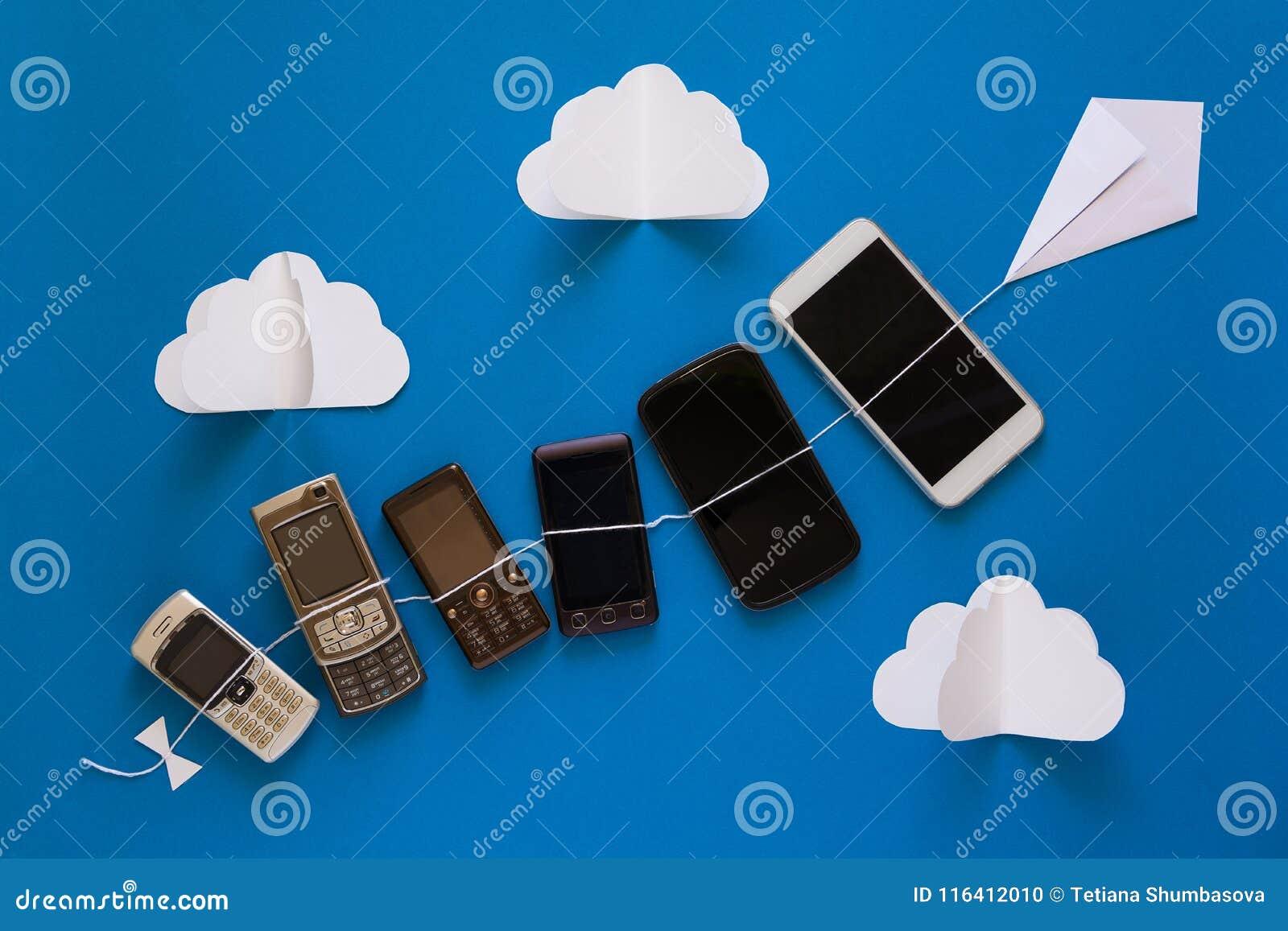 Het concept van de technologieevolutie Uitstekende en nieuwe telefoons die op document vlieger op blauwe hemel vliegen
