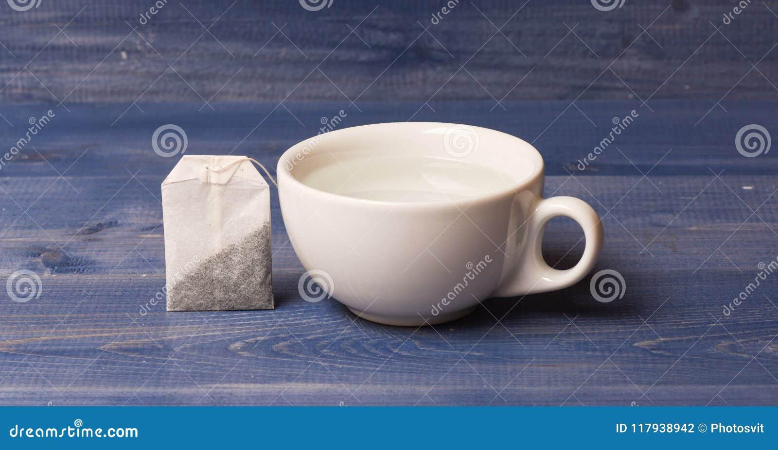 Het concept van de theetijd Kop of witte porseleinmok met transparante warm water en zak thee Proces die van thee binnen brouwen
