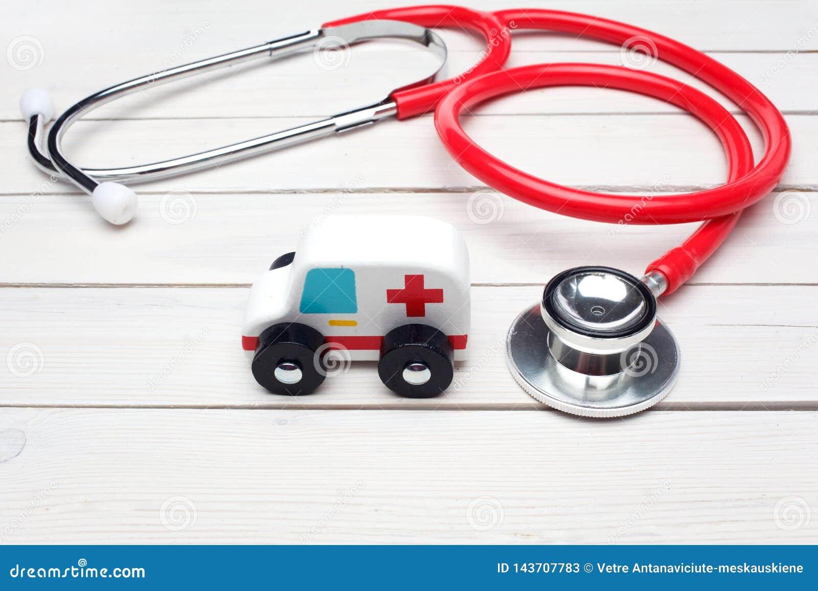 Het Concept van de ziekenwagendienst Het stuk speelgoed van het ziekenwagenvoertuig dichtbij stethoscoop op witte houten achtergr