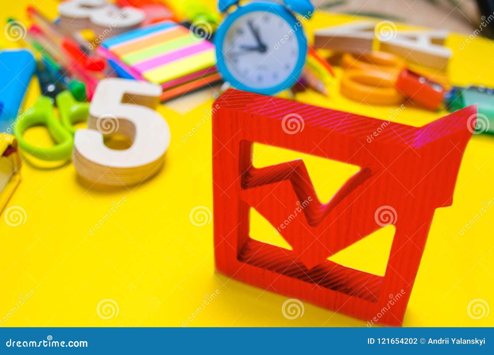 Het concept van schoolverkiezingen De doos en de schooltoebehoren van de verkiezingscontrole op een bureau op een gele achtergron