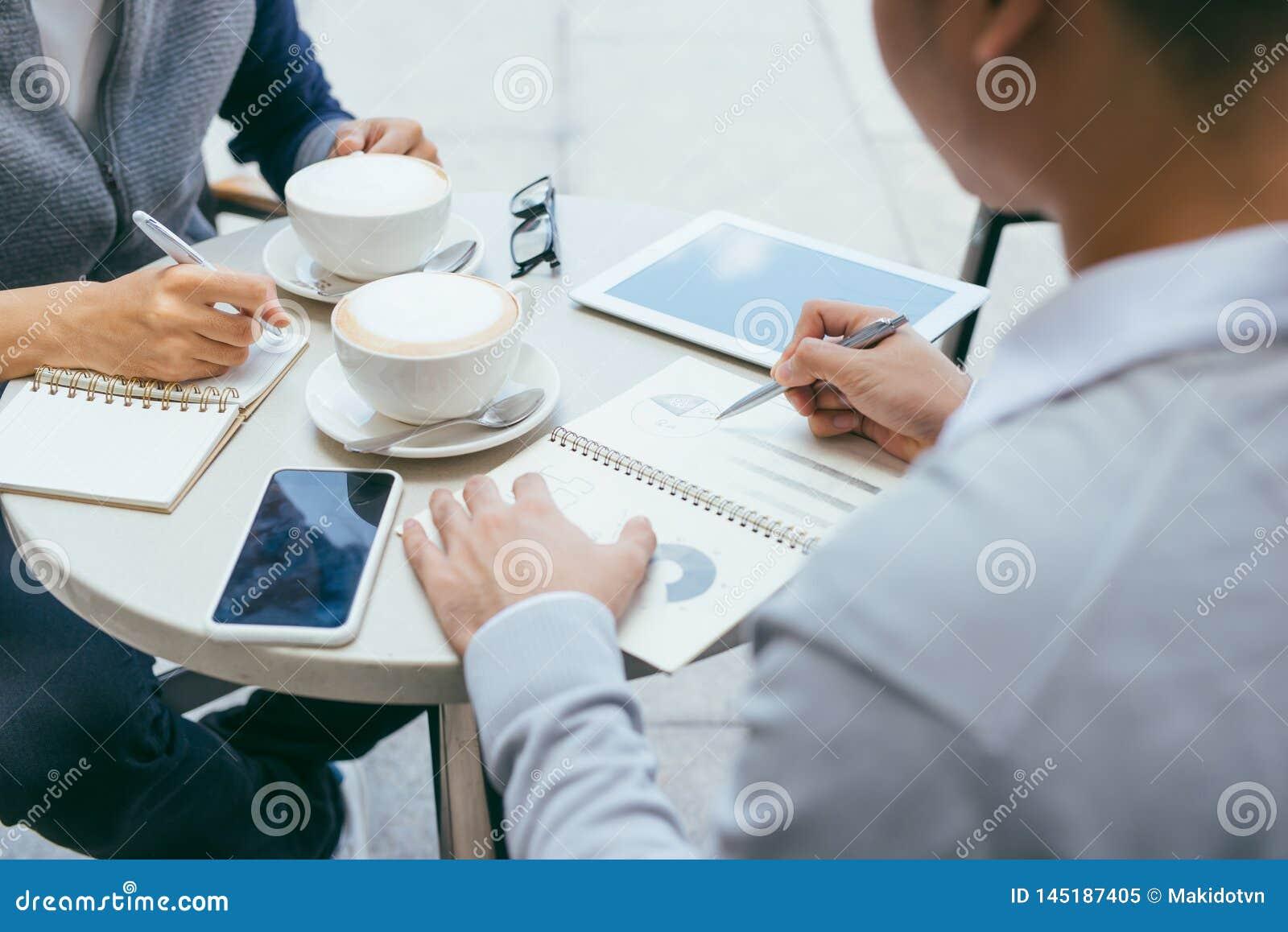 Het controleren van Voorraden Twee partners die aan laptop werken die cheerfully op een vergadering bij de lokale koffie glimlach