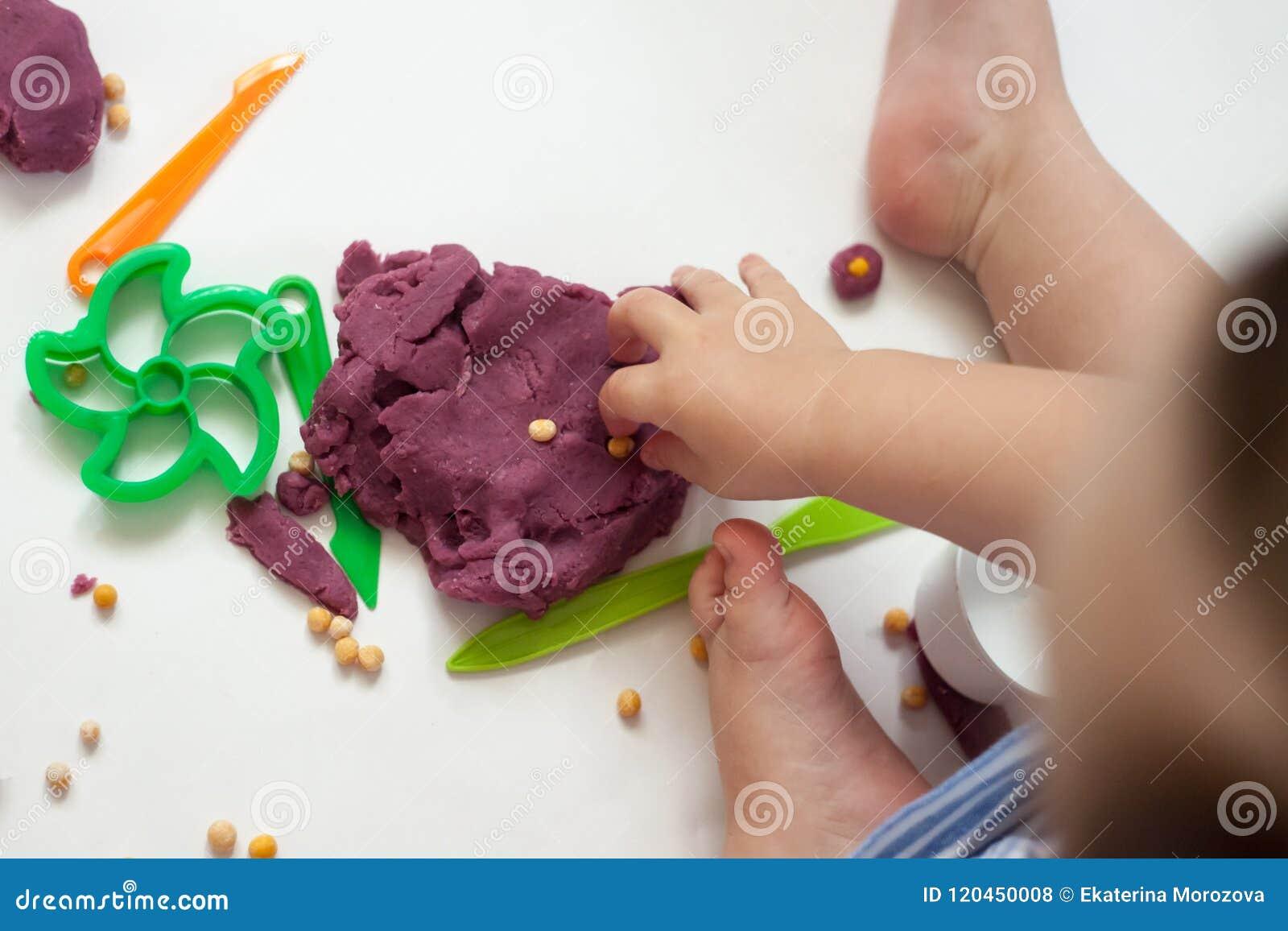 Het creatieve meisje spelen met kleurrijke modelleringsklei bij kleuterschool Weinig jong geitje die thuis vormen Ontwikkelingssp
