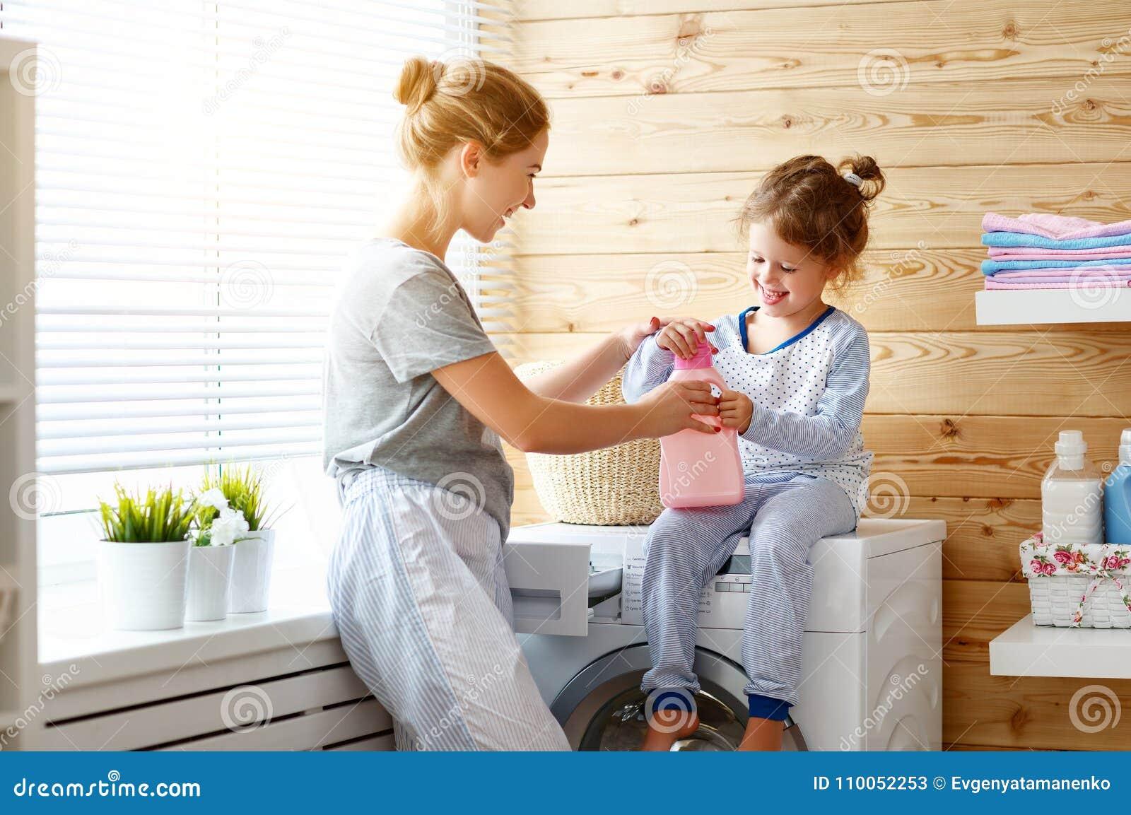 Het de gelukkige huisvrouw en kind van de familiemoeder in wasserij met washin