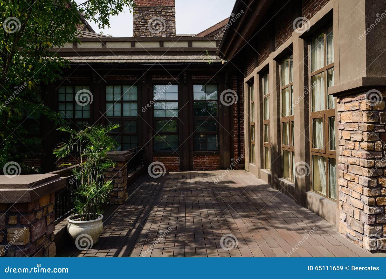 Het in de schaduw gestelde terras met planked vloer in de zonnige