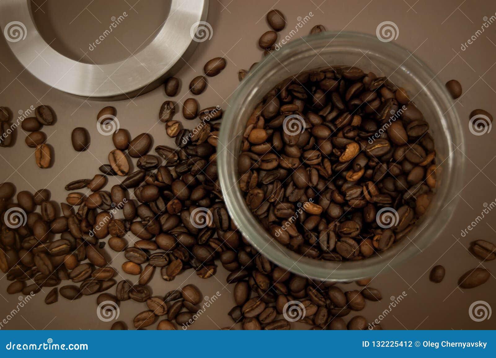 Het deksel en de koffiebonen van de koffiebus op de lijst worden verspreid die
