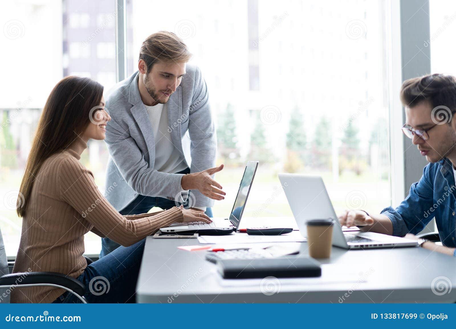 Het delen van adviezen Groep jonge moderne mensen die in slimme vrijetijdskleding zaken bespreken terwijl het werken in creatief