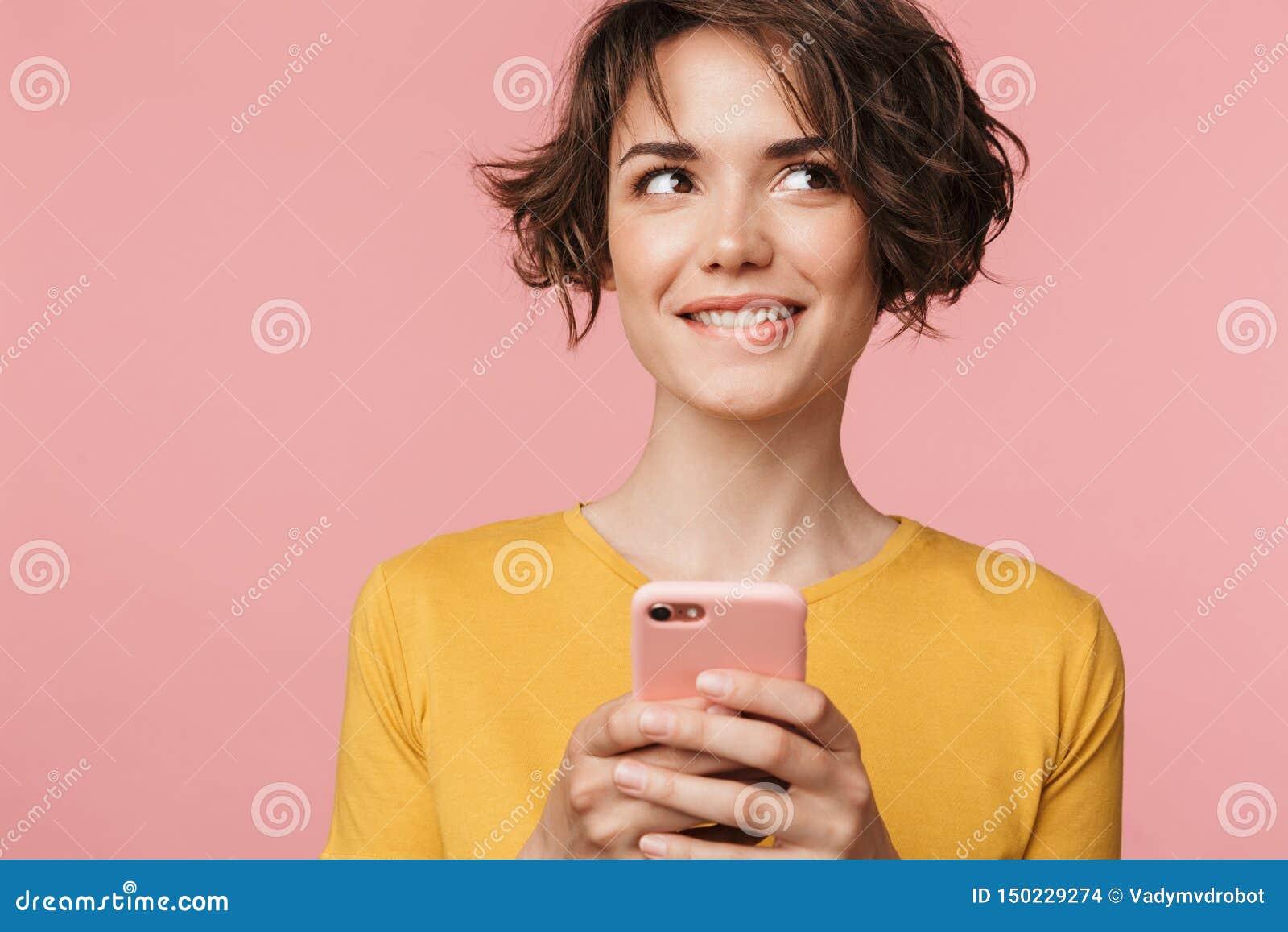 Het denken het dromen het jonge mooie vrouw stellen geïsoleerd over roze muurachtergrond die mobiele telefoon met behulp van