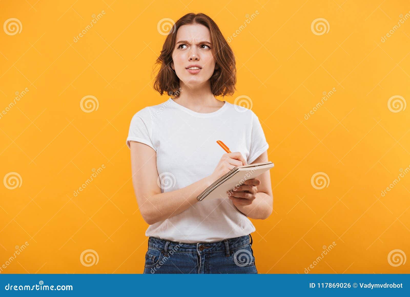 Het denken jonge vrouw het schrijven nota s Opzij het kijken