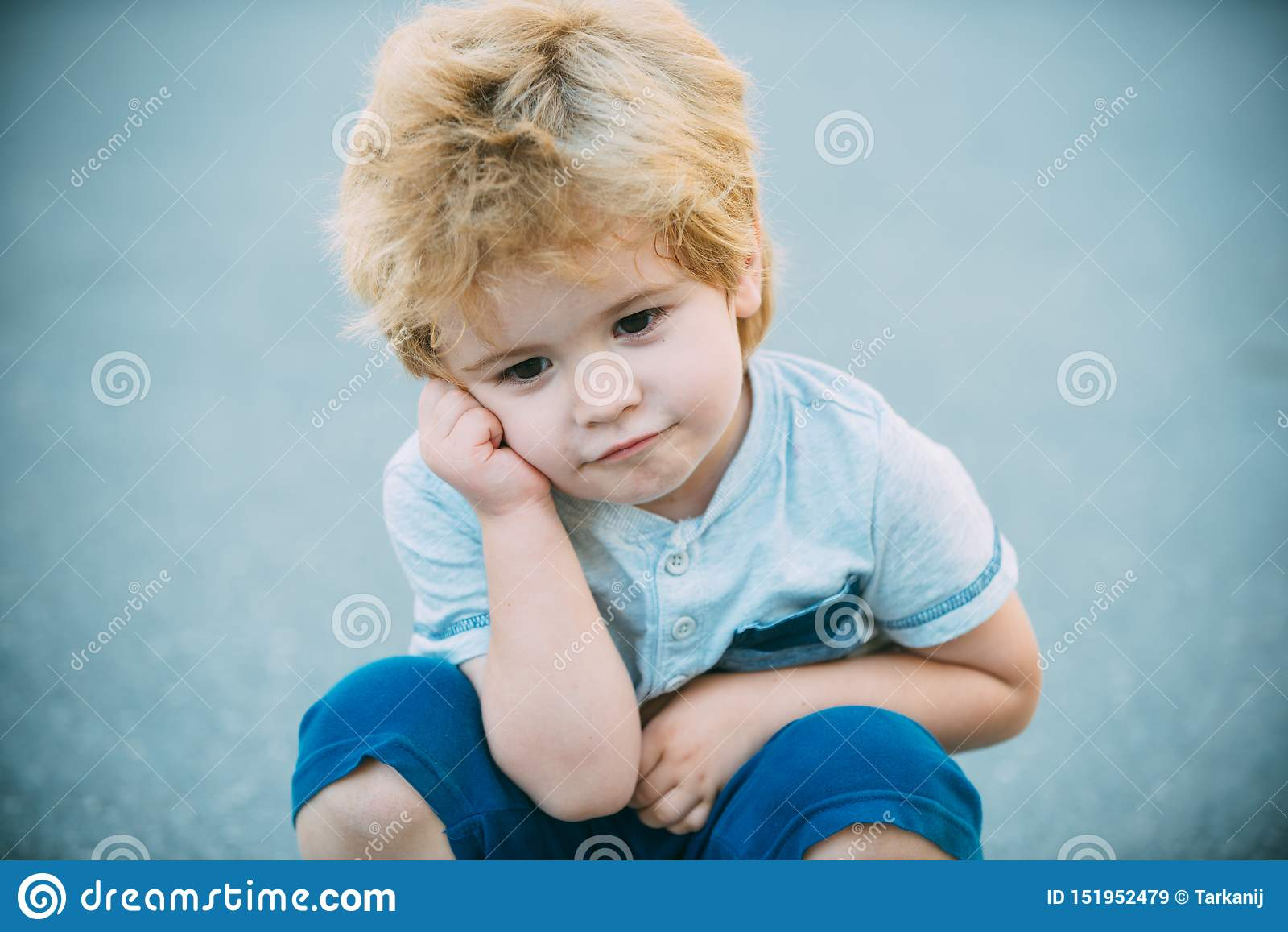 Het denken van de jongen Nadenkende kleuterjongen op blauwe wegachtergrond Notulenuitstel Het kind is vermoeid en