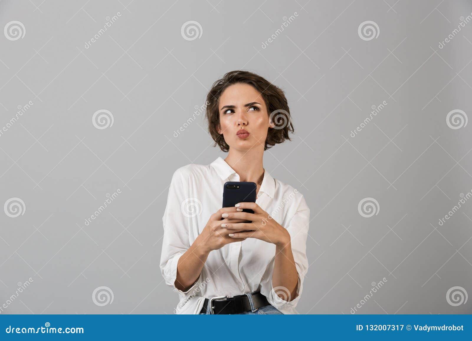 Het denken verwarde het jonge bedrijfsvrouw stellen geïsoleerd over grijze muurachtergrond gebruikend het mobiele telefoon babbel
