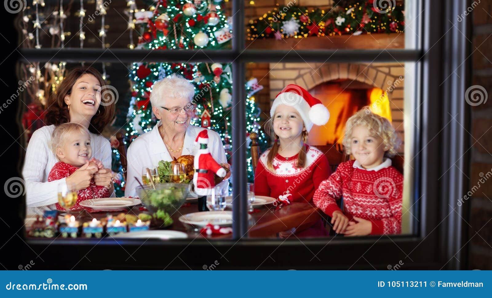 Het diner van Kerstmis Familie met jonge geitjes bij Kerstmisboom