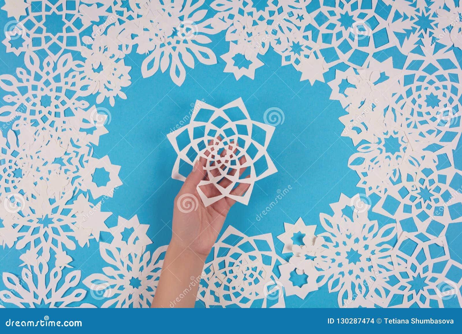 Het document van de handholding sneeuwvlok op blauwe achtergrond Hoogste mening De decoratie van Kerstmis