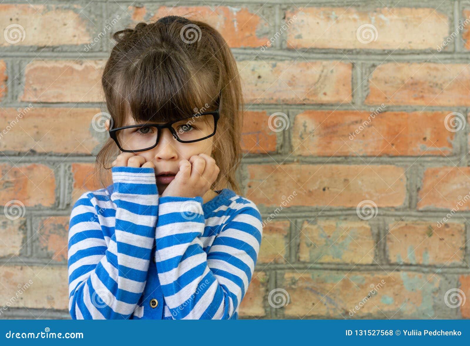 Het doen schrikken kind weinig jongen in witte t-shirt drukt verrukking bij een lege lege bakstenen muur uit