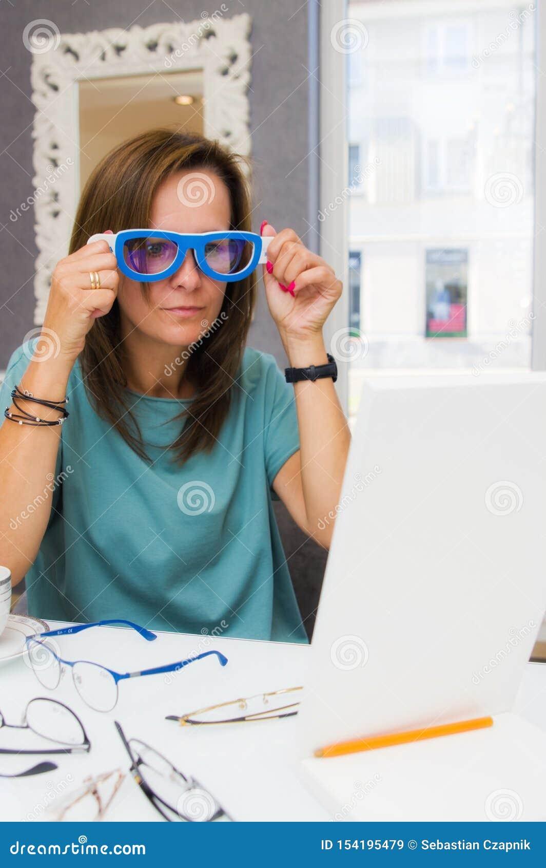 Het donkerbruine vrouw kiezen en het kopen oogglazen in opticiensalon of winkel