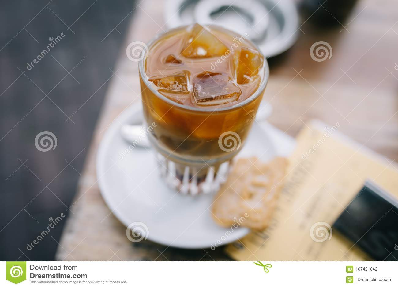 Het drinken van een bevroren koffie in de zomer met latte op een houten lijst