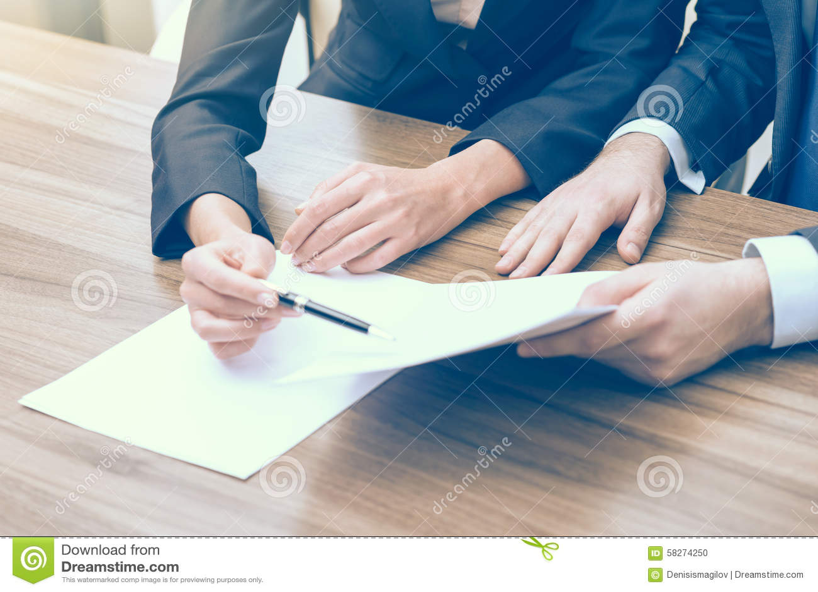 Het dubbel controleren van de essentiële informatie over bedrijfsproject Een paar in formele kleding bekijkt de documenten