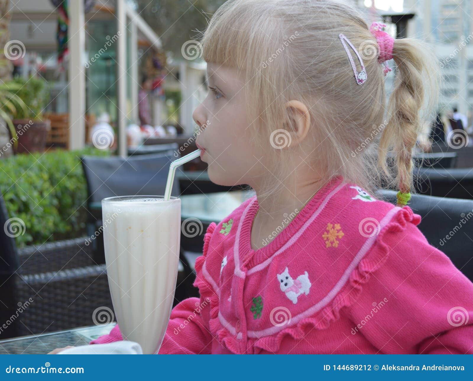 Het een weinig blonde meisje drinkt een norse milkshake