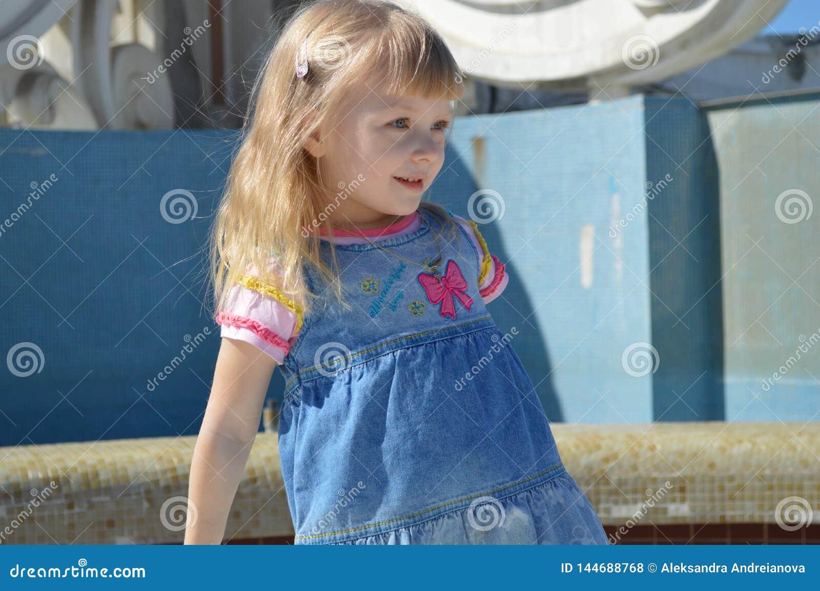Het een weinig mooie meisje glimlacht en onderzoekt de afstand