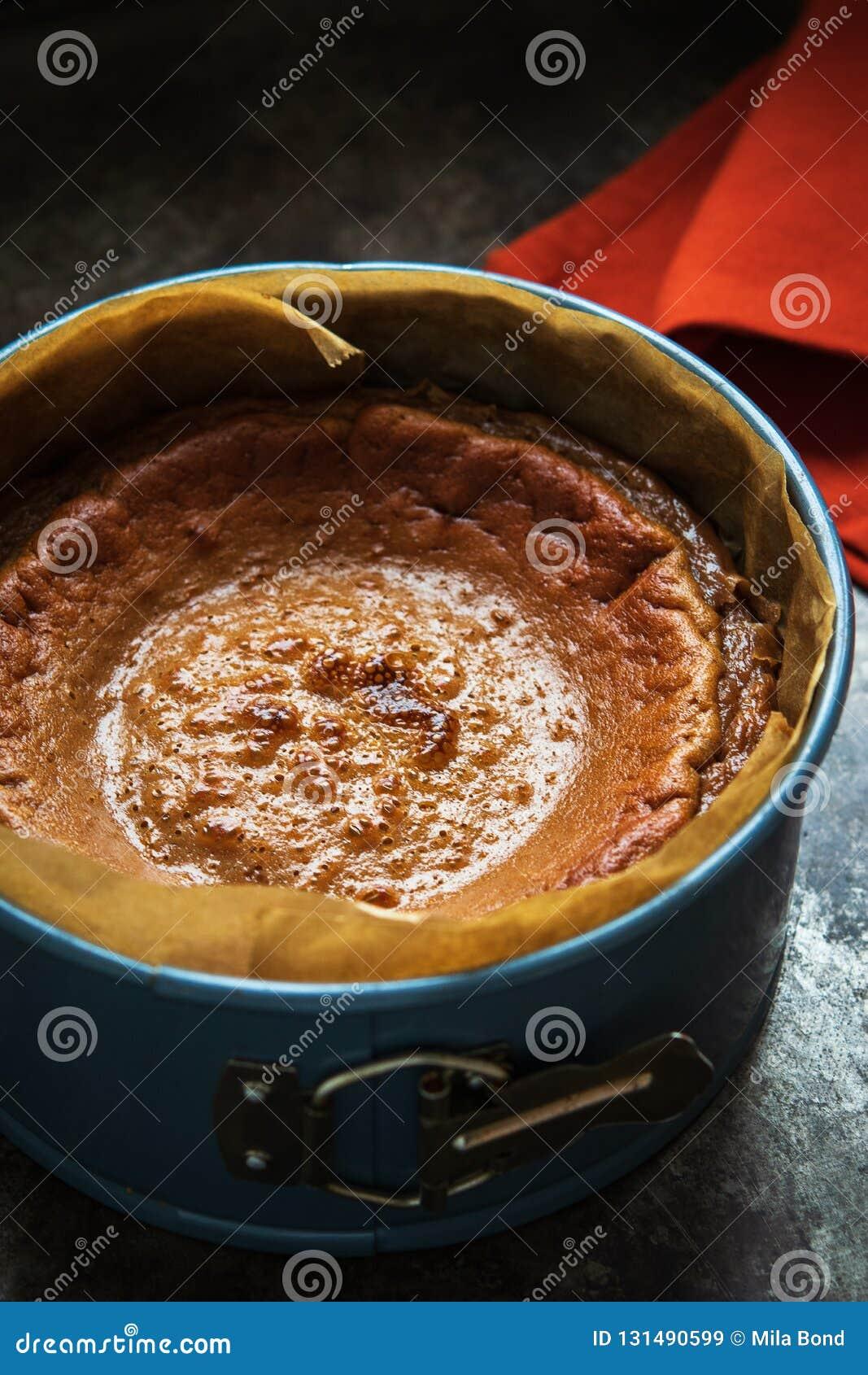 Het eindigen vers bakte karamelkaastaart in cakevorm op een donkere achtergrond
