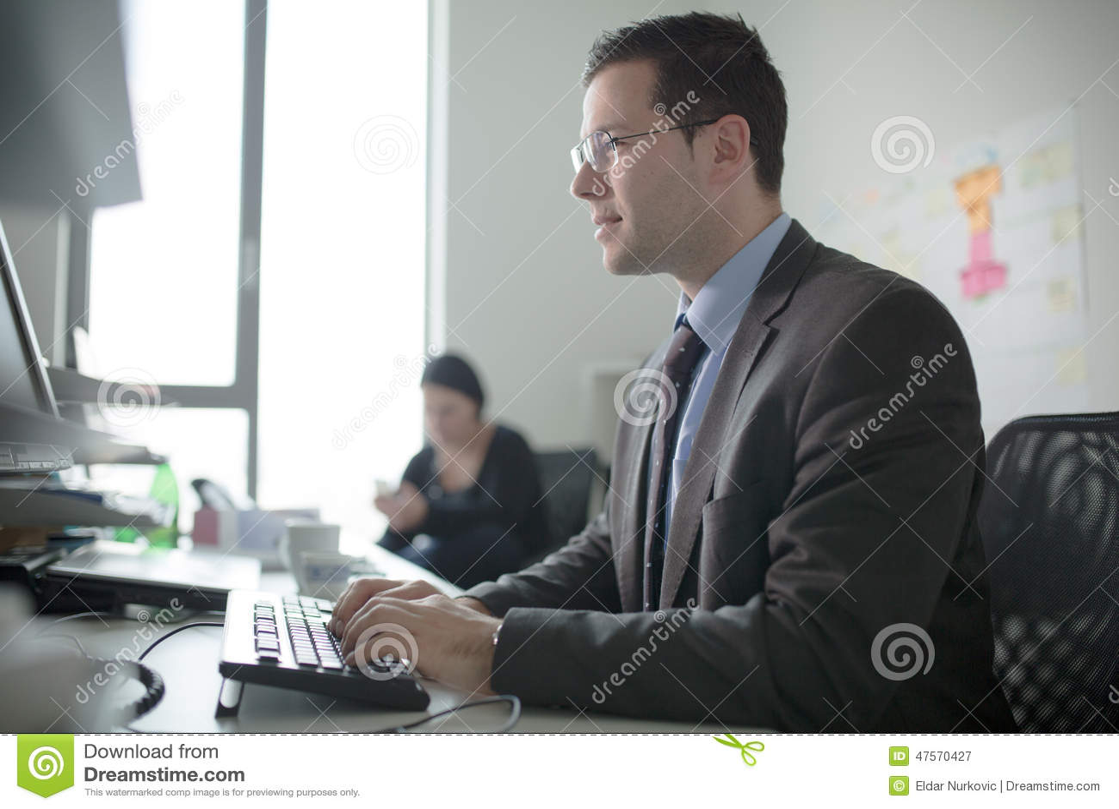 Het ernstige toegewijde bedrijfsmensenwerk in bureau op computer Echte econoom bedrijfsmensen, niet modellen Bankbedienden het be
