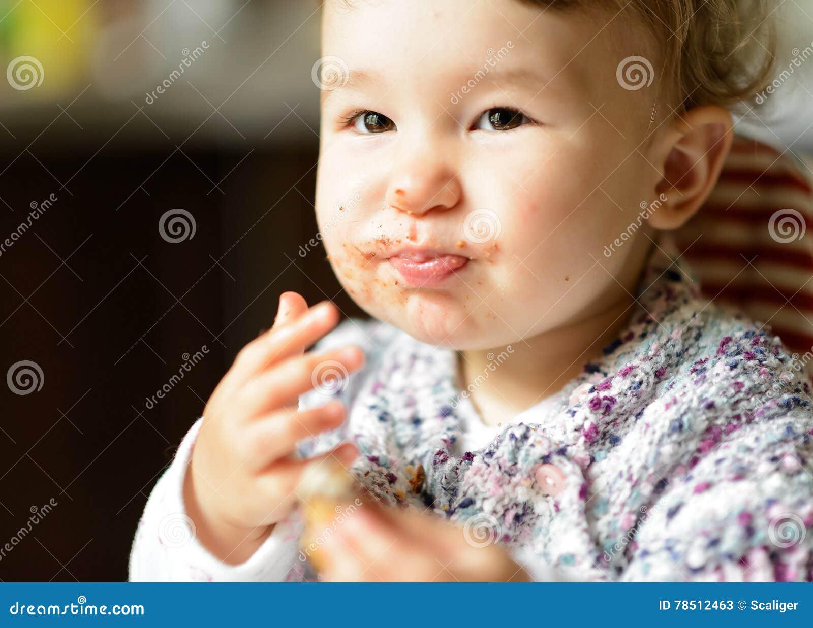 Het eten van vrolijk babymeisje met slordig gezicht
