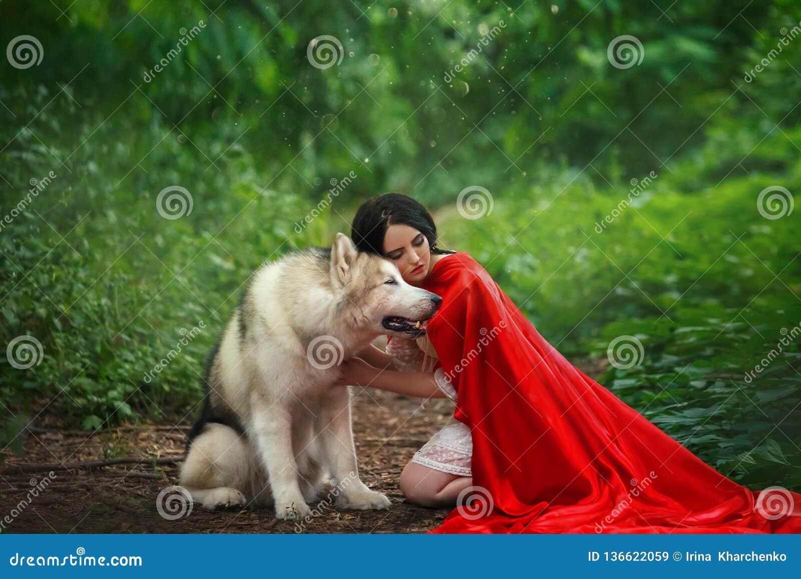 Het fabelachtige beeld, donker-haired donkerbruine aantrekkelijke dame in plotseling witte kleding, lange rode scharlaken mantel