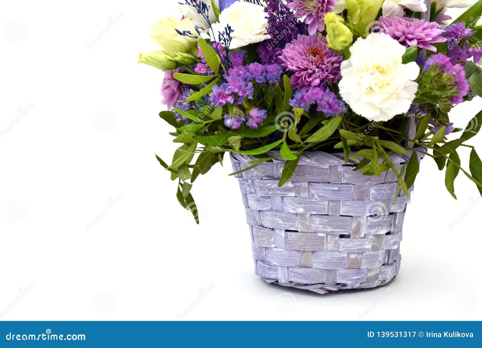 Het geïsoleerde boeket van de lente bloeit in decoratieve rieten houten mand van lilac en purpere bloemen op een witte achtergron