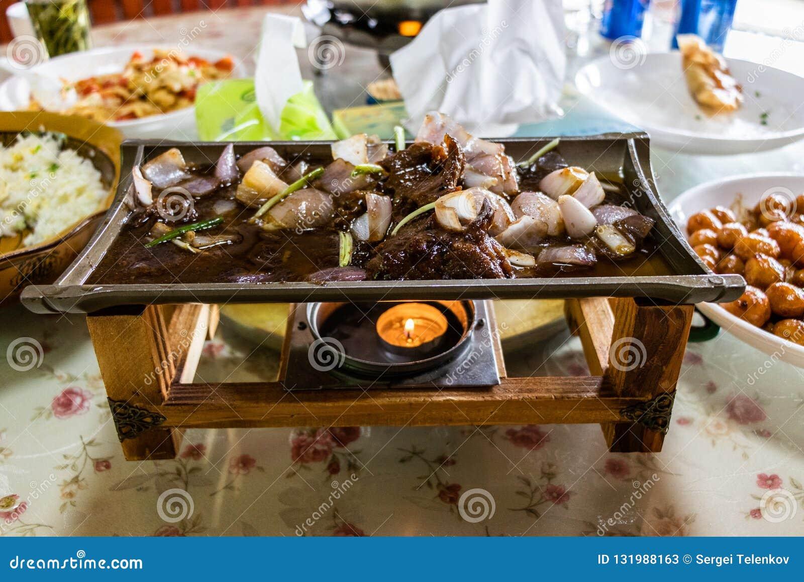 Het gebraden vlees en de groenten op een ceramische schotel, worden verwarmd op een houten tribune Sappig vlees, gebraden uien, a