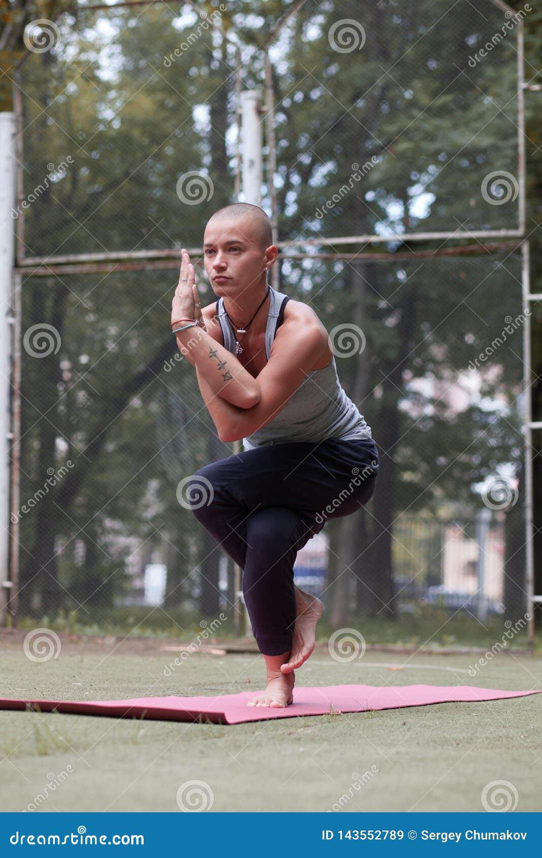 Het geconcentreerde wijfje in yogaadelaar stelt in groen park