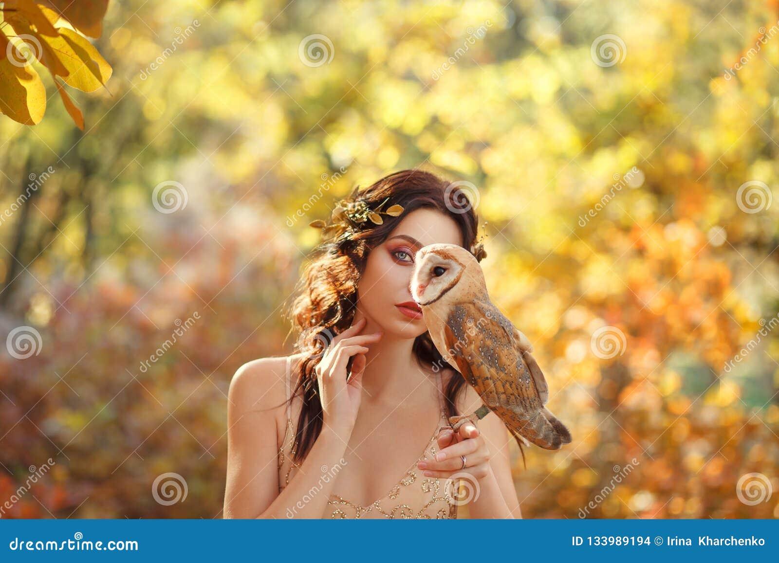 Het geheimzinnige meisje verbergt een deel van gezicht achter uilzitting op de vinger van een donker-haired aantrekkelijke dame,