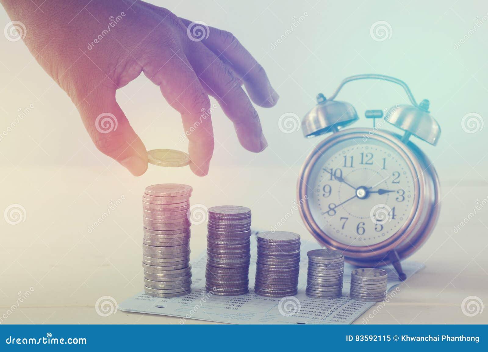 Het geld van de handholding op stapel van muntstukken en wekkerconcept spaart binnen