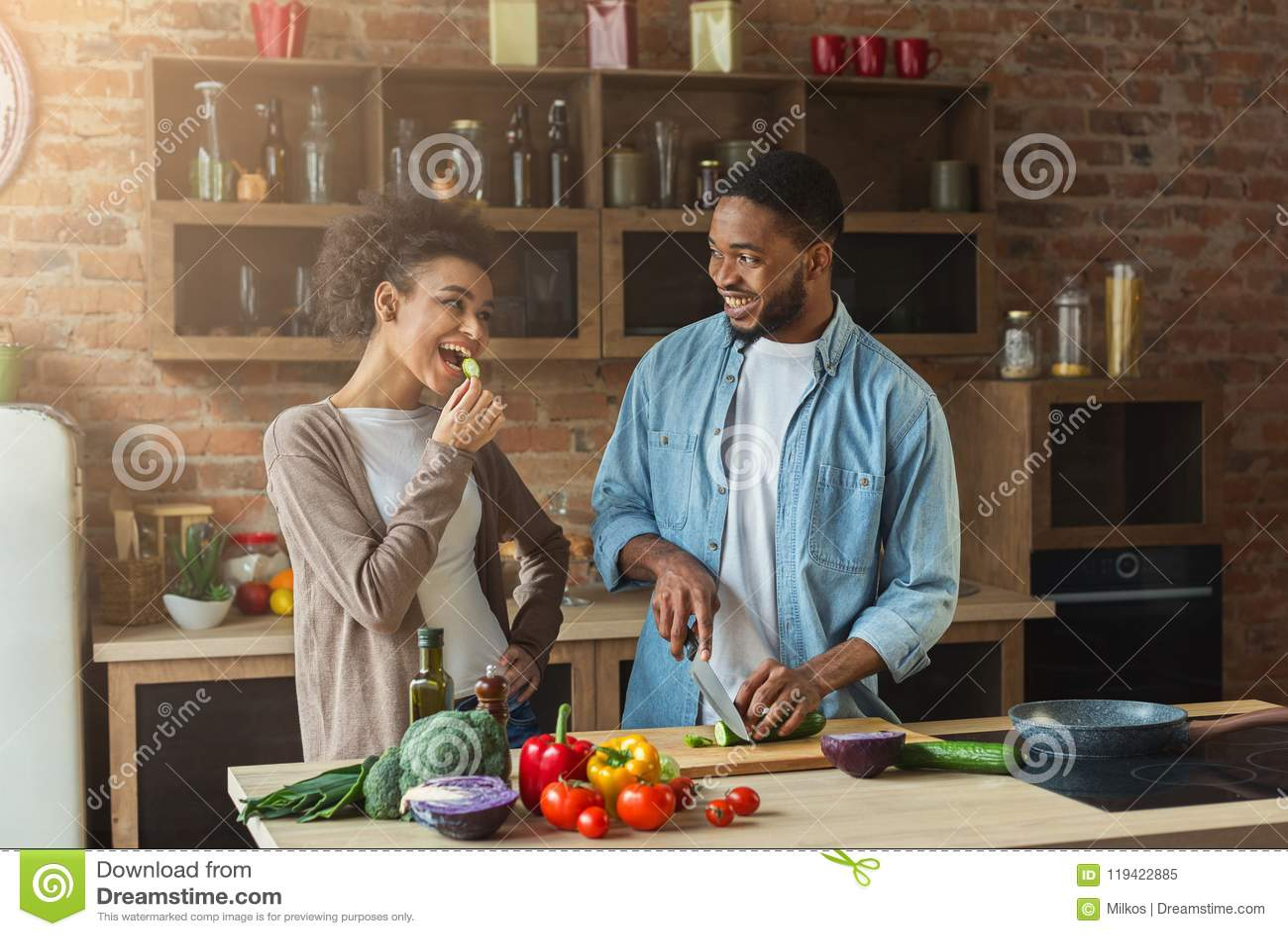 Het gelukkige Afrikaans-Amerikaanse paar koken in zolderkeuken