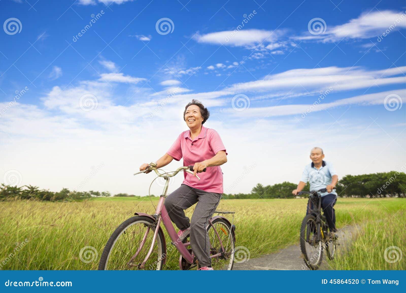 Het gelukkige Aziatische bejaarde oudstenpaar biking in landbouwbedrijf