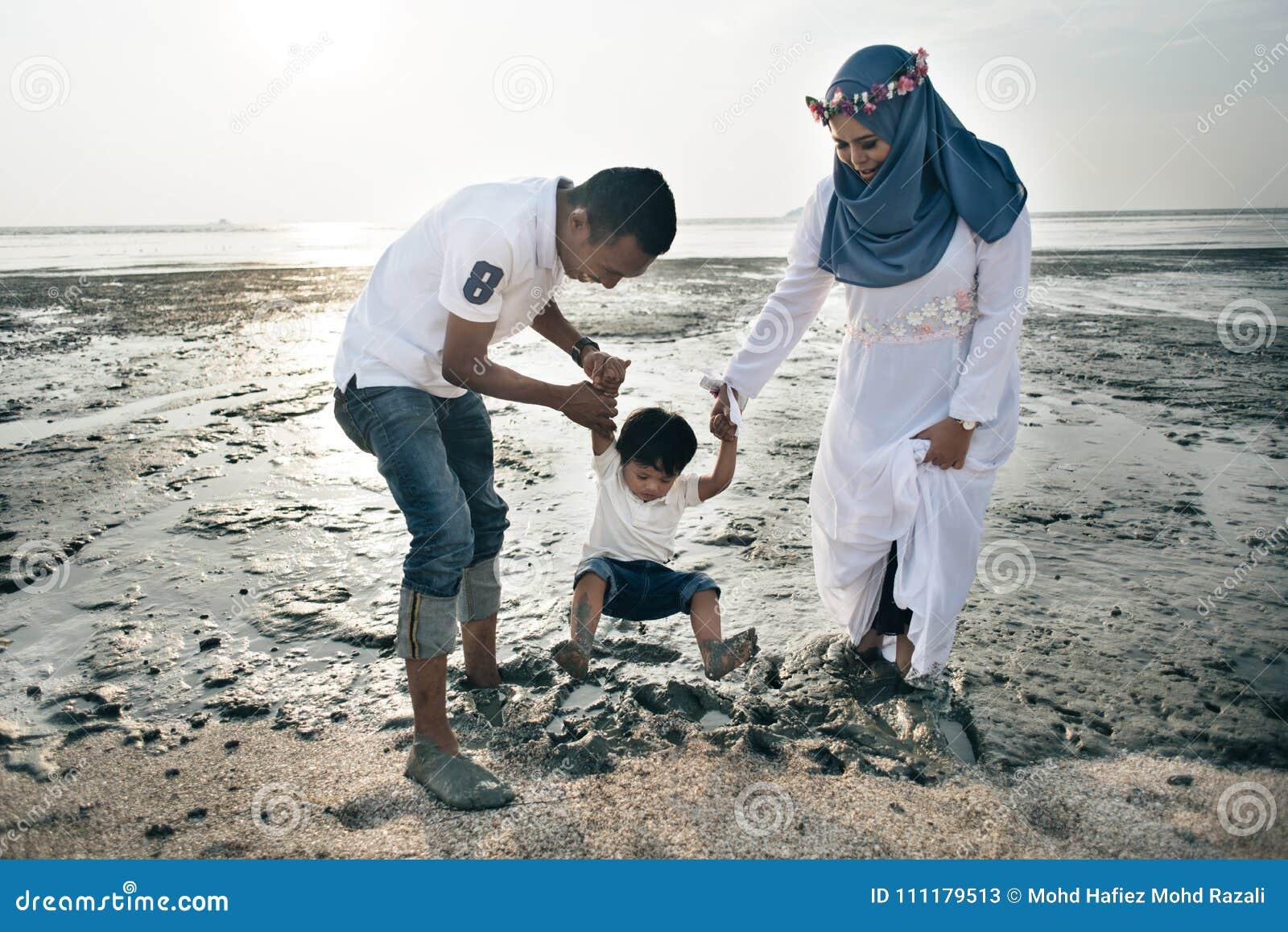 Het gelukkige Aziatische familie dragen toevallig en het spelen met modder bij het modderige strand