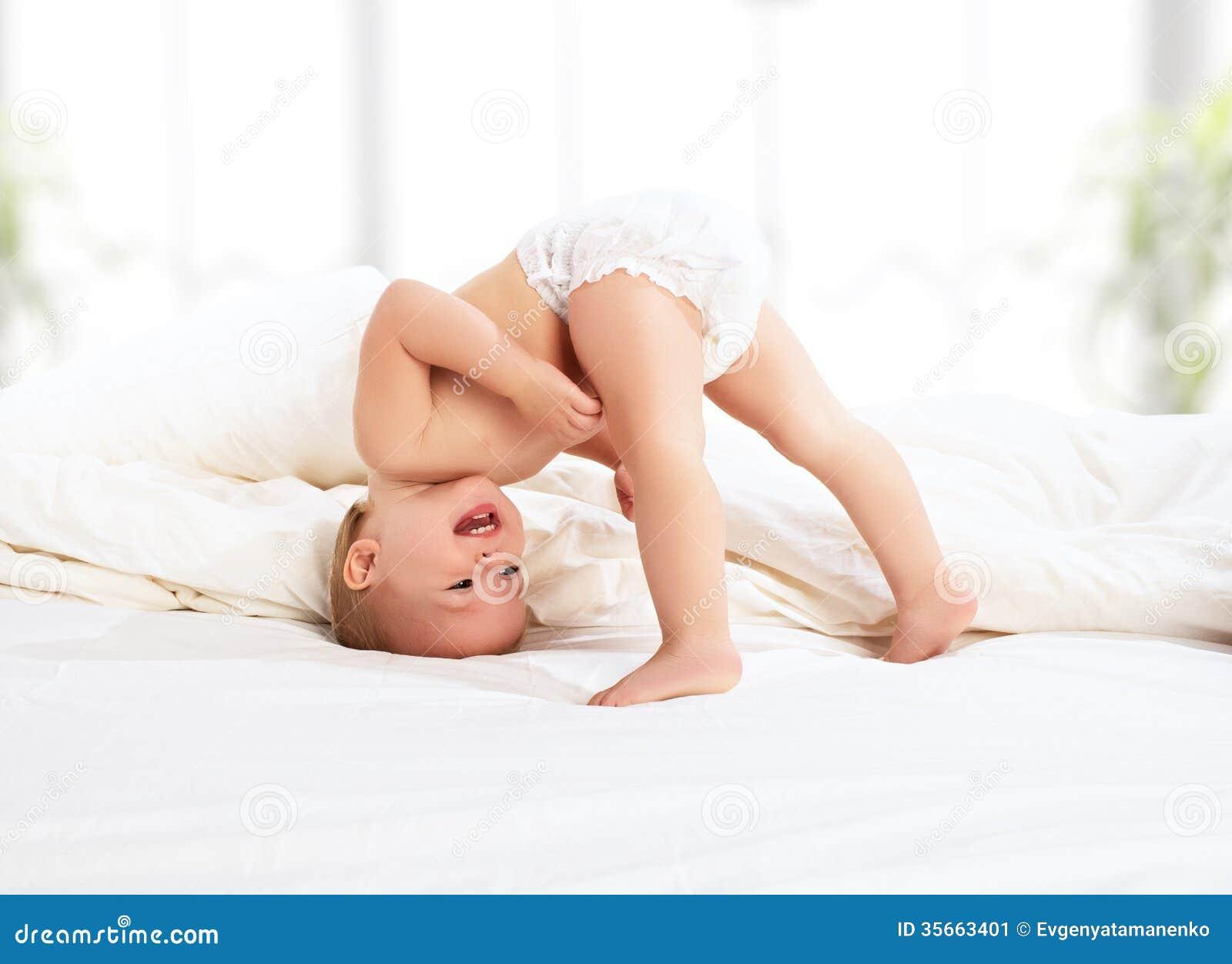 Het gelukkige babykind spelen   in bed