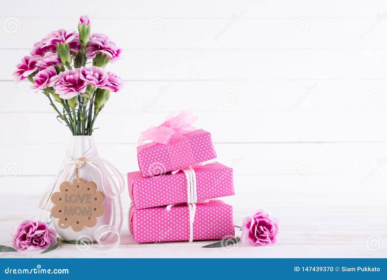 Het gelukkige concept van de moedersdag Giftvakje met roze anjerbloem op witte houten lijstachtergrond
