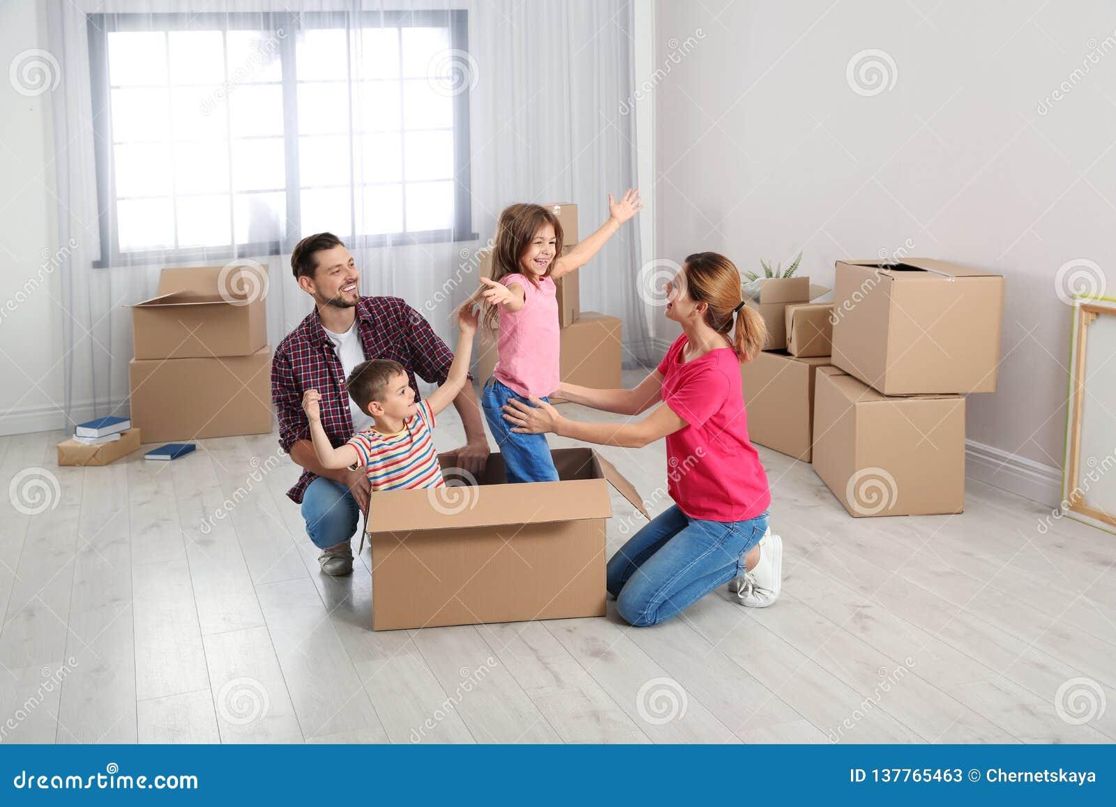 Het gelukkige familie spelen met kartondoos in hun huis Bewegende Dag