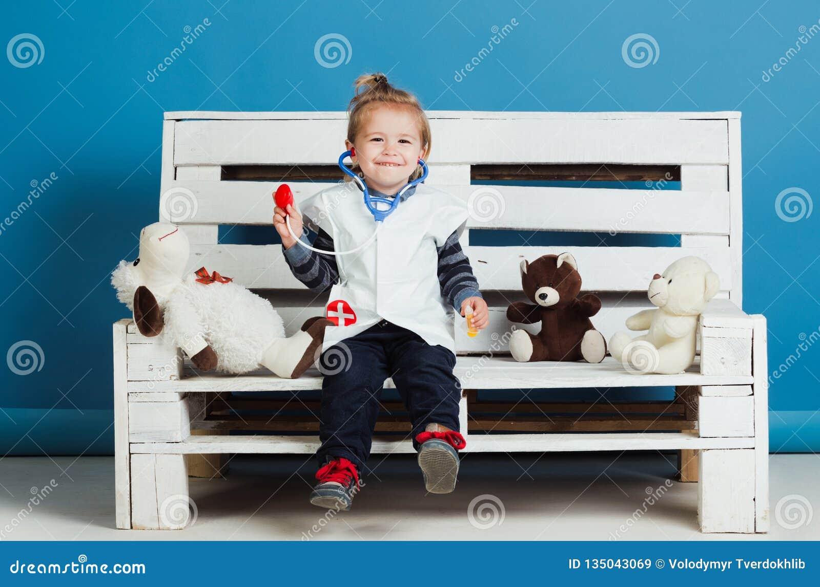 Het gelukkige jonge geitje met stuk speelgoed huisdieren zit op houten bank