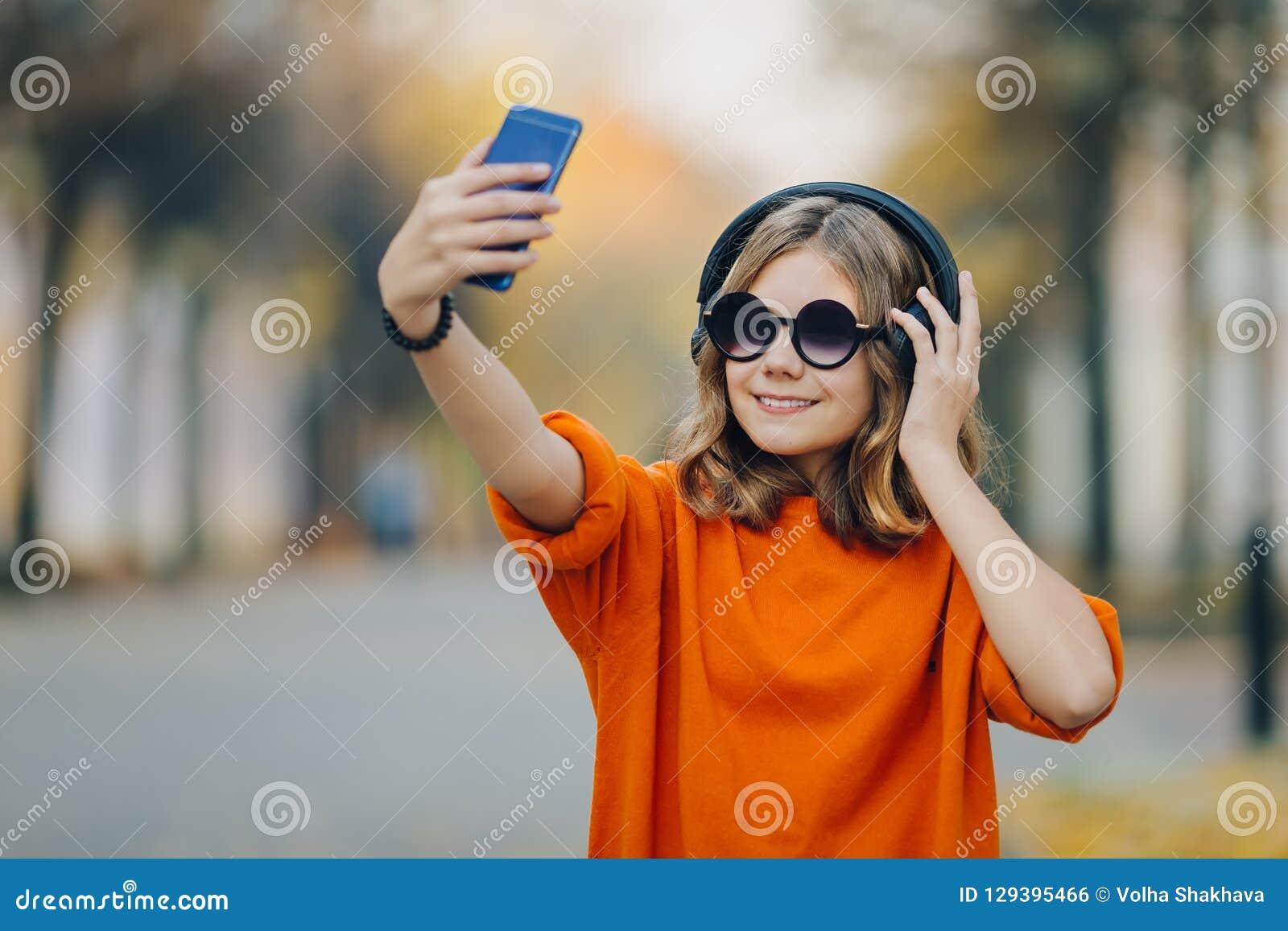 Het gelukkige jonge hipstermeisje op de straat neemt een foto op een smartphone Mooi blonde met hoofdtelefoons en smartphone