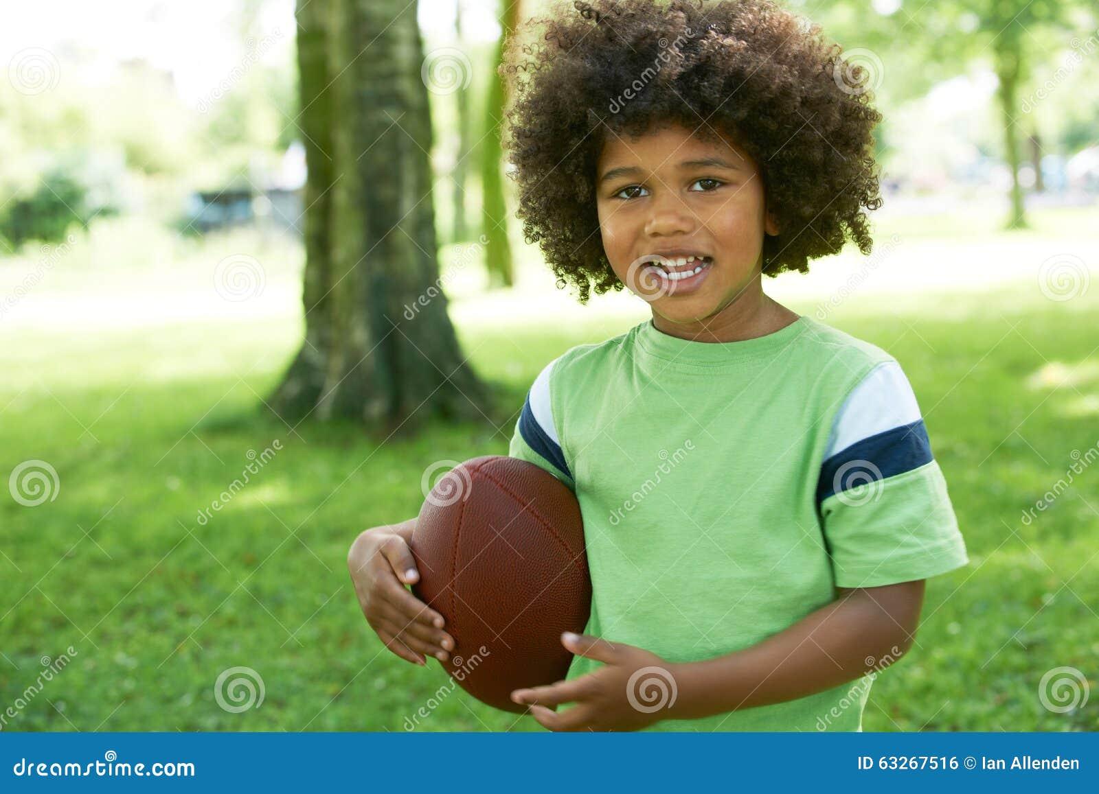 Het gelukkige Jonge Jongen Spelen in Park met Amerikaanse Voetbal