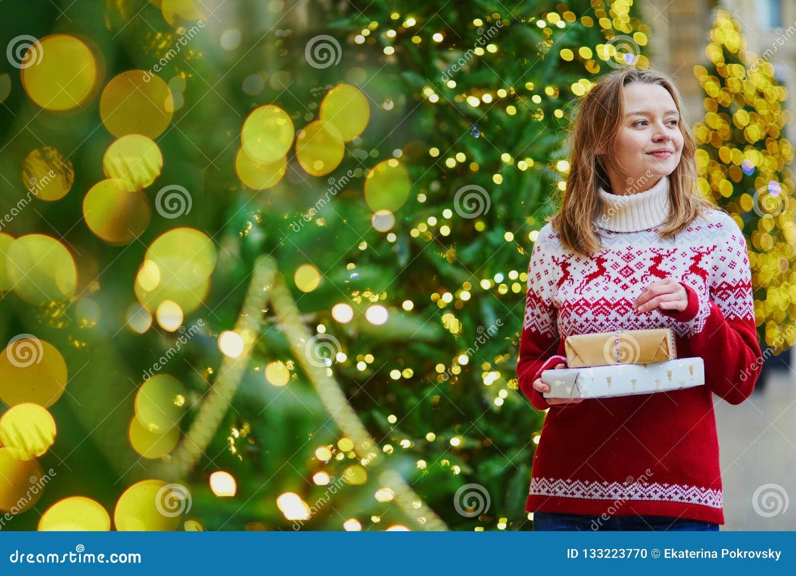 Het gelukkige jonge meisje in vakantiesweater met stapel van Kerstmis stelt voor