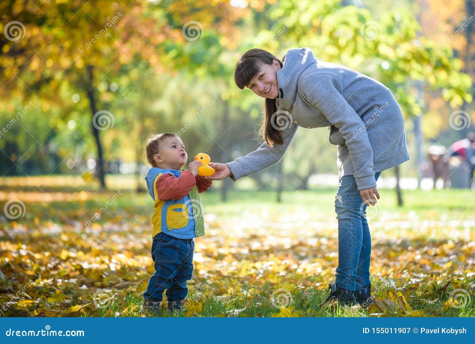 Het gelukkige jonge moeder spelen met baby in de herfstpark met gele esdoorn gaat weg Familie die in openlucht in de herfst lopen