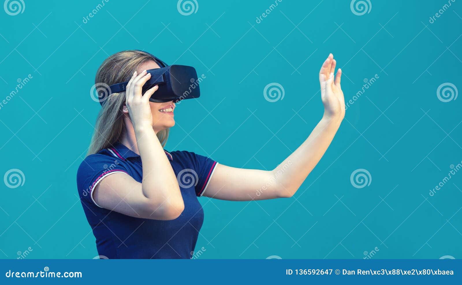 Het gelukkige jonge vrouw spelen op VR-glazen binnen Virtueel werkelijkheidsconcept met jong meisje die pret met hoofdtelefoonbes