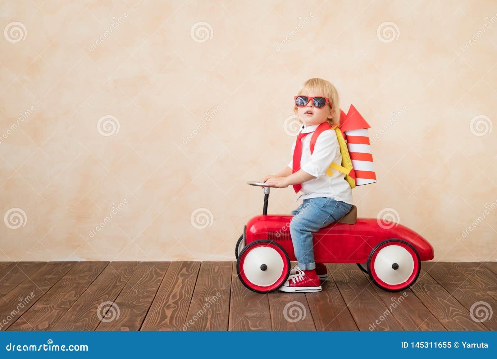 Het gelukkige kind spelen met stuk speelgoed raket thuis