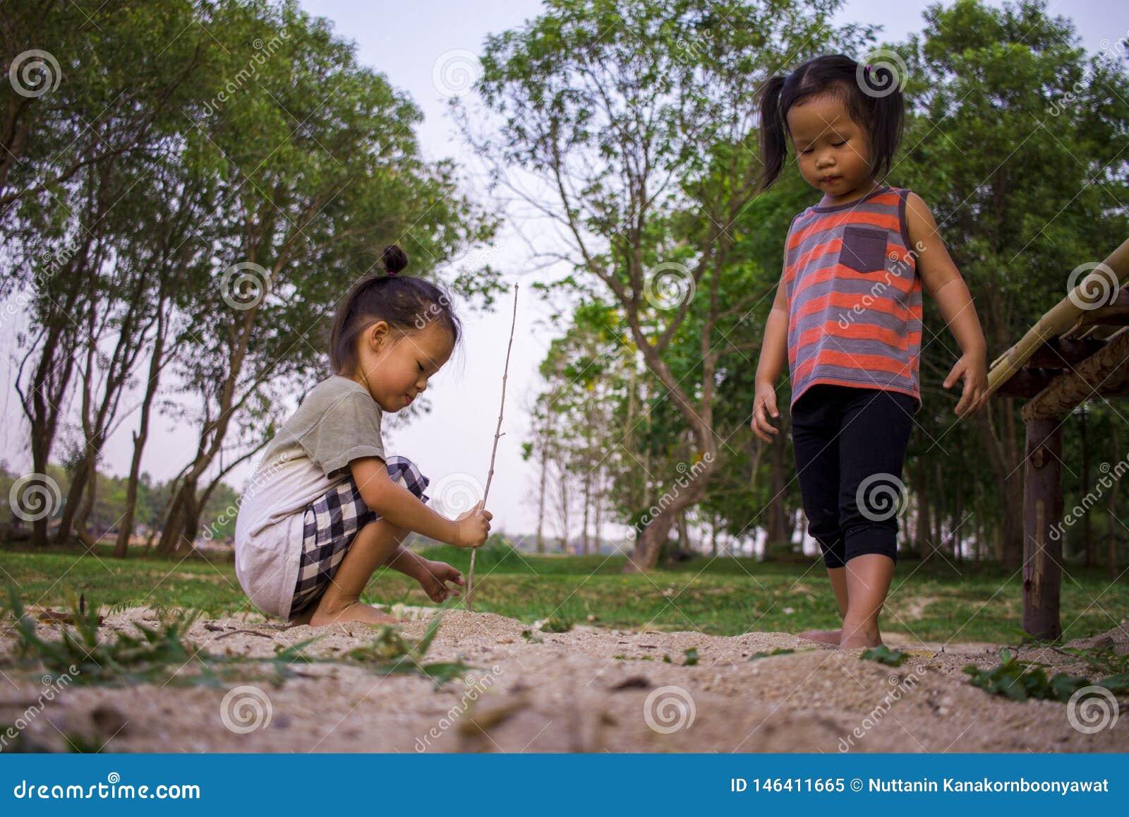 Het gelukkige kind spelen met zand, Grappige Aziatische familie in een park