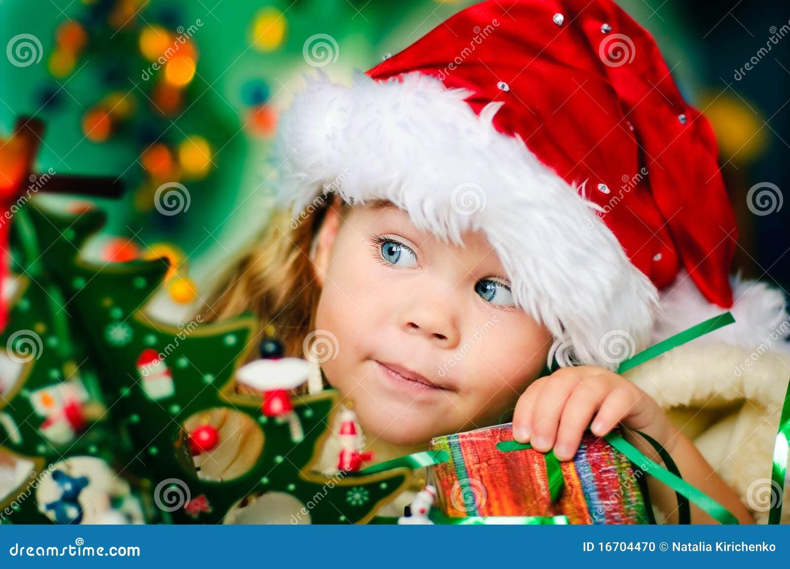 Het gelukkige kleine meisje in de hoed van de Kerstman heeft Kerstmis